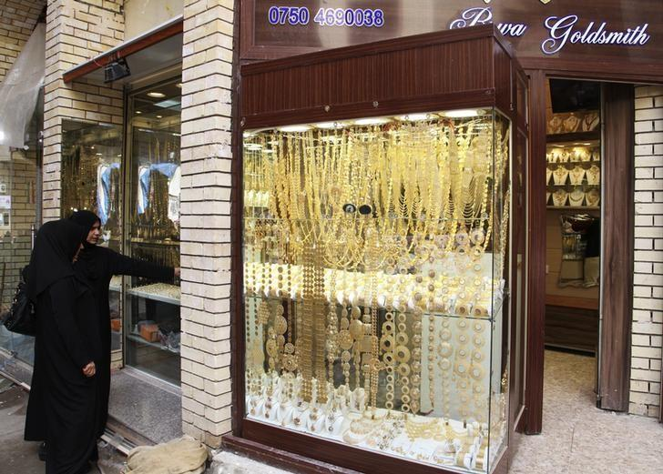 Women look at gold jewellery at a shop in a gold market in Arbil, in Iraq's Kurdistan region