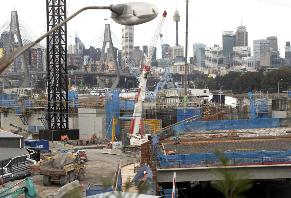 Construction teams work on a major road project in Sydney, Australia, Tuesday, May 11, 2021. The Australian government will release its big-spending economic plan for the next fiscal year on Tuesday designed to create jobs and repair pandemic damage and with an eye toward winning votes at looming general elections. (AP Photo/Mark Baker)