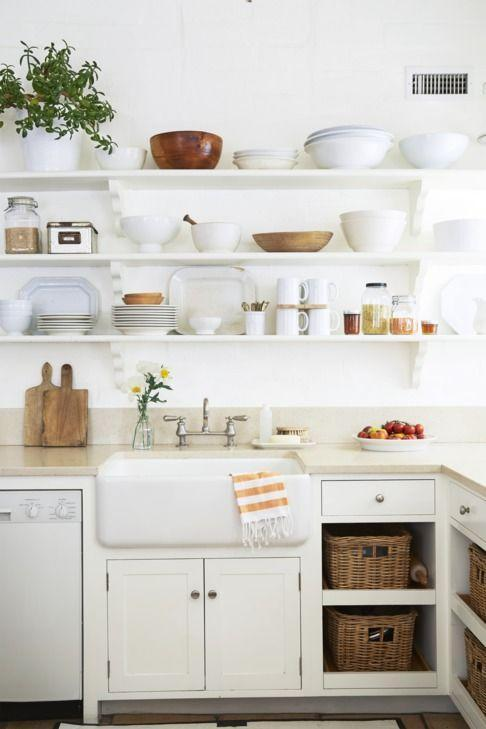 <p>To avoid a sterile look, opt for creamy whites inspired by the tones found in ironstone. A slightly darker countertop breaks up the wash of white and leads the way for other natural tones, like the wood cutting boards and storage baskets.</p>