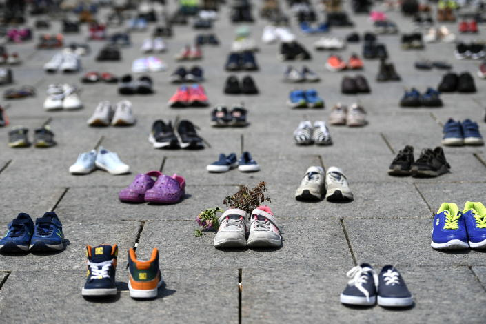 Dried flowers rest inside a pair of child's running shoes at a memorial for the 215 children whose remains were found at the grounds of the former Kamloops Indian Residential School at Tk'emlups te Secwépemc First Nation in Kamloops, B.C., on Parliament Hill in Ottawa on Friday, June 4, 2021. (Justin Tang/The Canadian Press via AP)