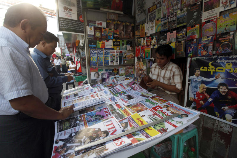 Customers buy weekly news journal at a roadside newspaper shop in Yangon, Myanmar, Friday, Dec. 28, 2012. Myanmar said Friday it will allow private daily newspapers starting in April for the first time since 1964, in the latest step toward allowing freedom of expression in the long-repressed nation. (AP Photo/Khin Maung Win)