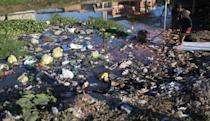 <p>A boy reaches for a ball along a polluted canal in the Mare favela community complex on July 18, 2016 in Rio de Janeiro, Brazil. Polluted canals in Rio such as this one empty in Guanabara Bay. The Mare complex is one of the largest favela complexes in Rio and is challenged by violence, pollution and poverty. The Rio 2016 Olympic Games begin August 5. (Mario Tama/Getty Images)</p>