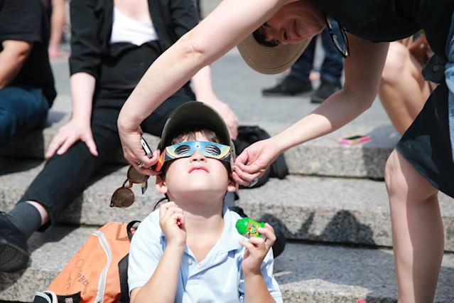 <p>People share glasses with a young boy to watch the total solar eclipse in Union Square, New York City, on Aug. 21, 2017. (Gordon Donovan/Yahoo News) </p>