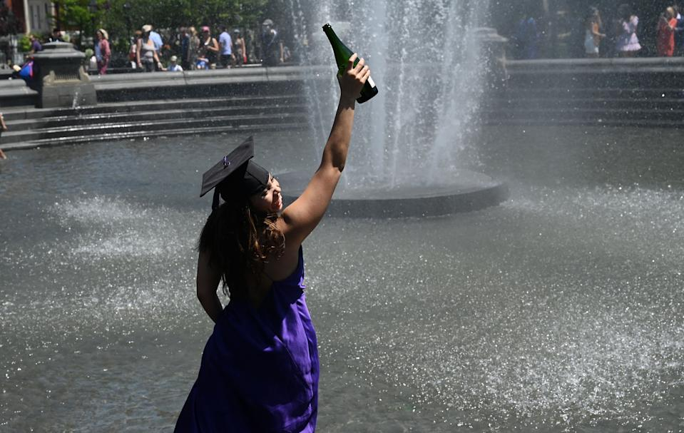 Student Annika Skuires drinks champagne in the fountain at Washington Square Park on May 19, 2021 in New York, after the New York University commencement ceremony was held virtually for the class of 2021. (Photo by TIMOTHY A. CLARY / AFP) (Photo by TIMOTHY A. CLARY/AFP via Getty Images)