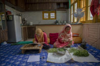 """Kashmiri student Aaishya Imtiyaz writes her examination as her mother Nusrat Fatima cleans vegetables inside their kitchen in Srinagar, Indian controlled Kashmir, Wednesday, July 22, 2020. Experts say lack of formal schooling during the lockdown could have a serious psychological and emotional impact on the children. With no opportunity to be with friends, many homebound students are struggling to reimagine the school experience as parents take over the role of teachers. """"This is my second exam at home since last year. I hope and pray that we go to school very soon,"""" Aaishya said. (AP Photo/Dar Yasin)"""