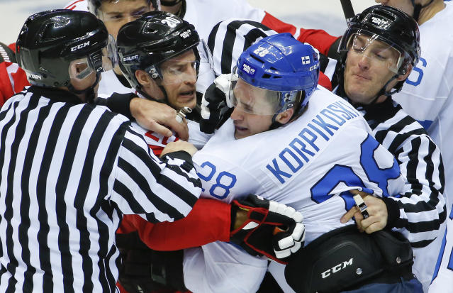 Referees break up a scuffle between Austria forward Daniel Welser (20) and Finland forward Lauri Korpikoski in the third period of a men's ice hockey game at the 2014 Winter Olympics, Thursday, Feb. 13, 2014, in Sochi, Russia. (AP Photo/Mark Humphrey)