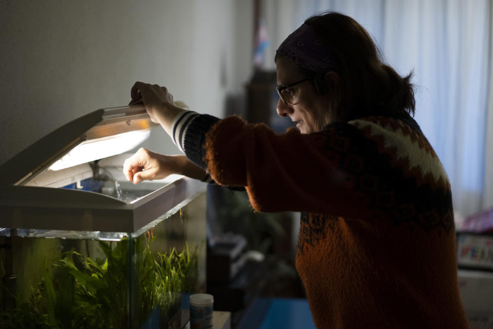 "Victoria Martinez, 44, feeds her fish at her home in Barcelona, Spain, Monday, Feb. 8, 2021. By May this year, barring any surprises, Martinez will complete a change of both gender and identity at a civil registry in Barcelona, finally closing a patience-wearing chapter that has been stretched during the pandemic. The process, in her own words, has also been ""humiliating."" (AP Photo/Emilio Morenatti)"
