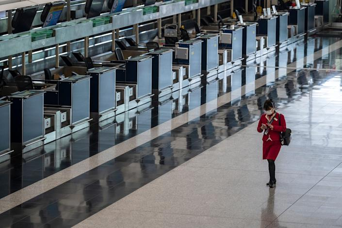 A Cathay Pacific Flight attended is seen walking pass empty check in counters inside the terminal of the Hong Kong International Airport on February 22, 2020 i 2