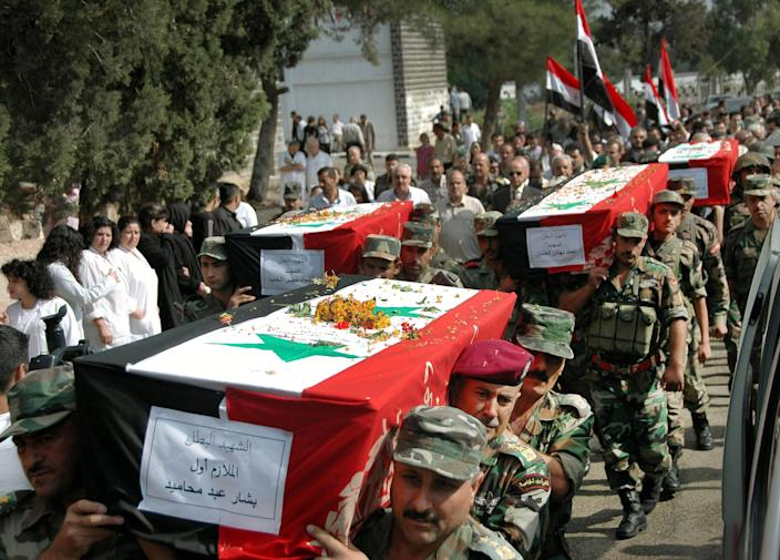 FILE - In this Oct. 1, 2011 file photo released by the Syrian official news agency SANA, Syrian army soldiers carry the coffins of their comrades who were killed in recent violence in the country, during their funeral procession at the military hospital in Homs, Syria. A top Syrian cleric's appeal for men to join the army raises the question of whether President Bashar Assad is running out of soldiers and prompts a pro-government newspaper to declare the military can battle insurgents for years to come. The civil war has eroded one of the Arab world's biggest armies, and pro-Assad militiamen are increasingly filling in for troops. ( (AP Photo/SANA, File)