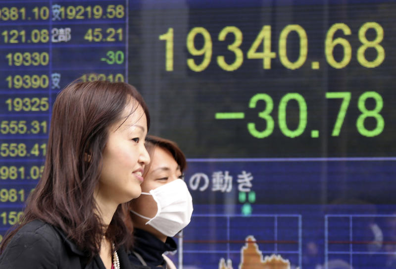 People walk by an electronic stock board of a securities firm in Tokyo, Friday, Feb. 24, 2017. Asian markets slipped in muted trading Friday amid worries over U.S. trade policies that may affect regional economies. A stronger yen weighed on Japan's exporters. (AP Photo/Koji Sasahara)