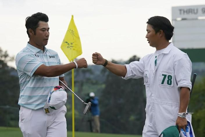 Hideki Matsuyama is congratulated by caddie Shota Hayafuji after shooting a seven-under 65 at the Masters on April 10, 2021.