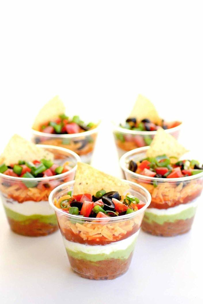 """<p>Individual cups of this delicious dip make it easy for friends and family to mingle during your springtime get-together. </p><p><em><u>Get the recipe at <a href=""""http://www.the-girl-who-ate-everything.com/2011/12/individual-seven-layer-dips.html"""" rel=""""nofollow noopener"""" target=""""_blank"""" data-ylk=""""slk:The Girl Who Ate Everything."""" class=""""link rapid-noclick-resp"""">The Girl Who Ate Everything.</a></u></em></p>"""