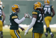Green Bay Packers quarterback Aaron Rodgers is congratulated by teammate Billy Turner (77) after Rodgers' touchdown pass to Marquez Valdes-Scantling against the Tampa Bay Buccaneers during the first half of the NFC championship NFL football game in Green Bay, Wis., Sunday, Jan. 24, 2021. (AP Photo/Matt Ludtke)