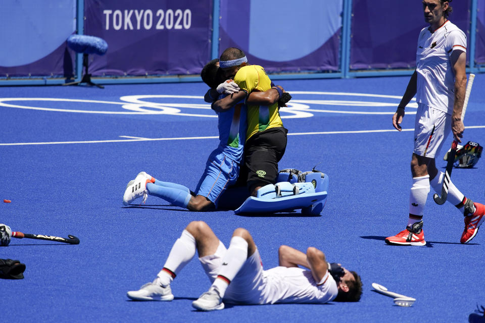 India's Surender Kumar, top left, and India goalkeeper Sreejesh Parattu Raveendran, top right, celebrate while Germany's Lukas Windfeder, bottom, reacts after India won their men's field hockey bronze medal match 5-4 at the 2020 Summer Olympics, Thursday, Aug. 5, 2021, in Tokyo, Japan. (AP Photo/John Locher)