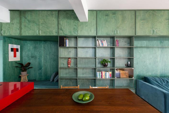 Turquoise shelves and cabinets run all along the interiors of the Point Supreme-renovated apartment.