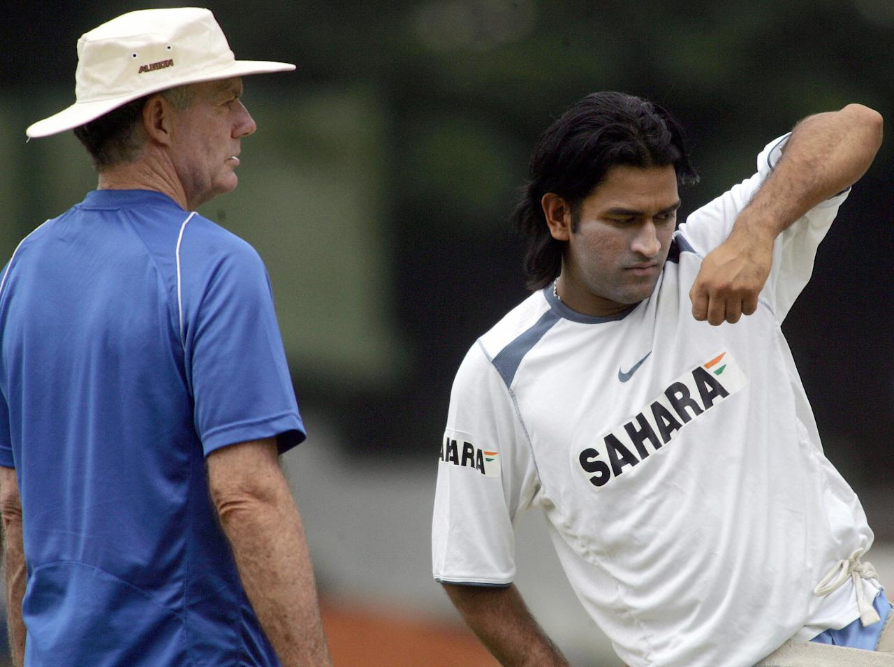 Bangalore, INDIA:  Indian cricket coach Greg Chappell (L) looks on as Mahendra Singh Dhoni practices a batting technique during a practice session at The National Cricket Academy (NCA) in Bangalore, 02 September 2006.  A nine day long training camp for Indian cricketers in preparation for the forthcoming tri-series with Australia and West indies in Malaysia, is continuing in the southern Indian city.    AFP PHOTO/Dibyangshu SARKAR  (Photo credit should read DIBYANGSHU SARKAR/AFP/Getty Images)
