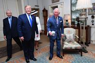 The Prince of Wales picks up a diffuser that fell off a waiting photographers flash as he enters a room with Duchess of Cornwall (2nd right) at Clarence House in London to take tea with US President Donald Trump (2nd left) and his wife Melania (behind).
