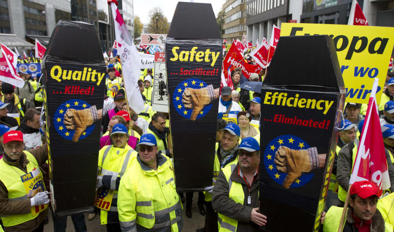 Airport ground workers and baggage handlers demonstrate with messages on mock coffins in front of EU headquarters in Brussels on Monday, Nov. 5, 2102. Workers are protesting against a proposal for more competition in the market which they feel will have a negative effect on their working conditions. (AP Photo/Virginia Mayo)