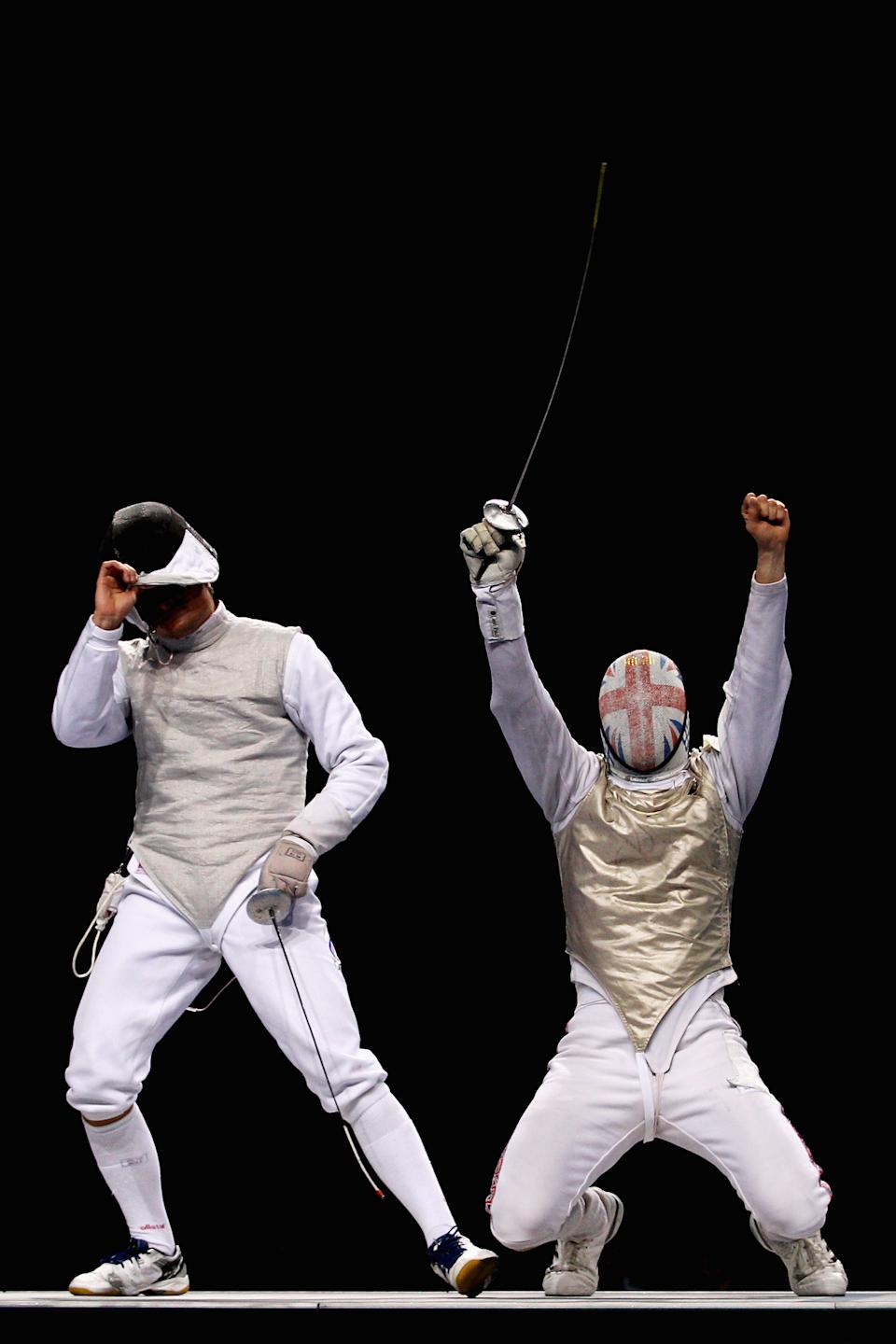 LONDON, ENGLAND - NOVEMBER 27: Dmitri Rigine (L) of Russia looks dejected as Richard Kruse celebrates winning the gold medal win in the Men's Foil Team Final at the Fencing Invitational, part of the London Prepares series at ExCel on November 27, 2011 in London, England (Photo by Dean Mouhtaropoulos/Getty Images)