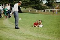 <p>Prince Philip stops to chat with two toddlers in 1980.</p>