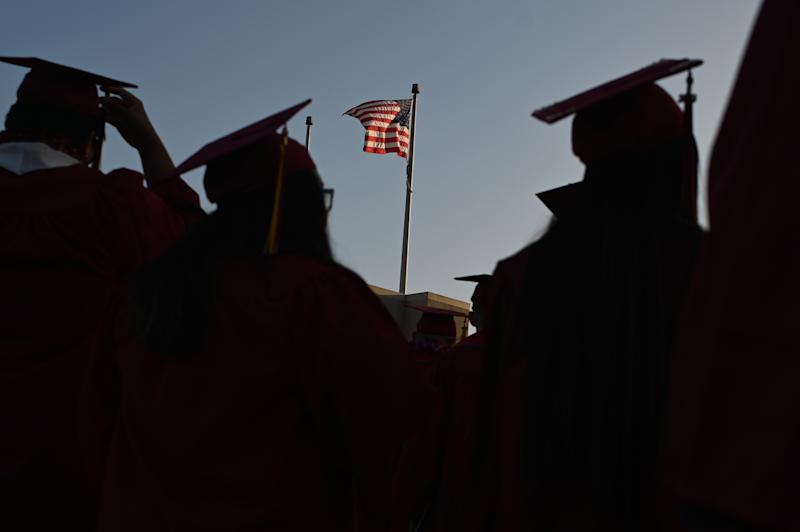 "A US flag flies above a building as students earning degrees at Pasadena City College participate in the graduation ceremony, June 14, 2019, in Pasadena, California. - With 45 million borrowers owing $1.5 trillion, the student debt crisis in the United States has exploded in recent years and has become a key electoral issue in the run-up to the 2020 presidential elections. ""Somebody who graduates from a public university this year is expected to have over $35,000 in student loan debt on average,"" said Cody Hounanian, program director of Student Debt Crisis, a California NGO that assists students and is fighting for reforms. (Photo by Robyn Beck / AFP) (Photo credit should read ROBYN BECK/AFP/Getty Images)"