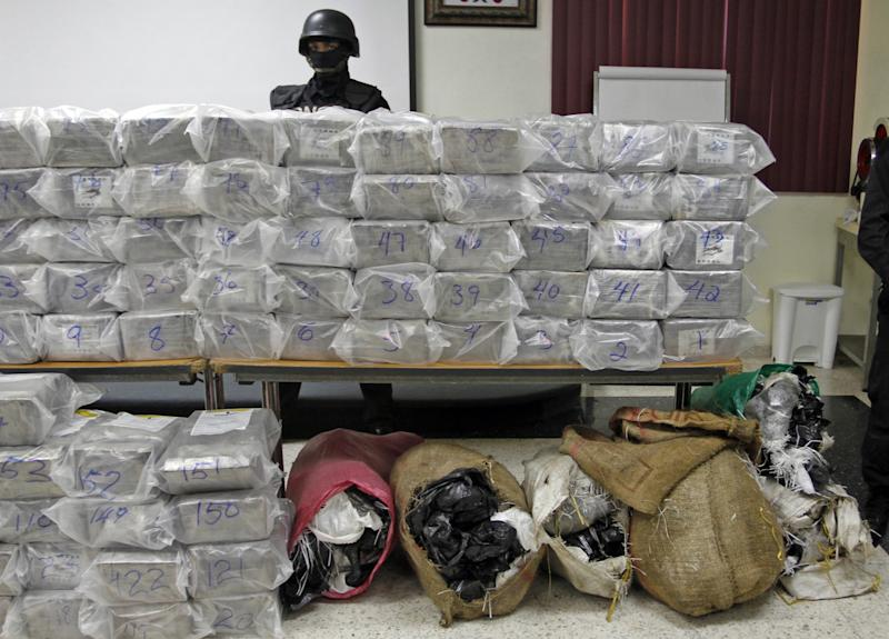 In this Oct. 8, 2013 photo, a Dominican anti-drug police officer stands behind packages of seized drugs during a news conference at the National Drug Control Agency in Santo Domingo, Dominican Republic. The Dominican Republic is now the region's biggest transit point for drugs. A U.S. military assessment projected that 6 percent of the cocaine destined for the U.S. this year will pass through the Dominican Republic alone. (AP Photo/Manuel Diaz)