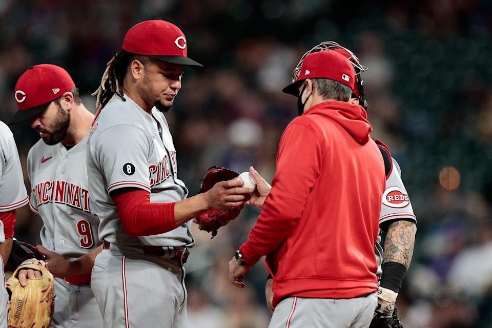 Reds pitcher Luis Castillo hands the ball to manager David Bell after giving up eight earned runs in 3 2/3 innings vs. the Rockies on May 13.