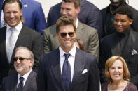 Tampa Bay Buccaneers quarterback Tom Brady, center, surrounded by members of the Tampa Bay Buccaneers, attends a ceremony on the South Lawn of the White House, in Washington, Tuesday, July 20, 2021, where President Joe Biden honored the Super Bowl Champion Tampa Bay Buccaneers for their Super Bowl LV victory. (AP Photo/Andrew Harnik)