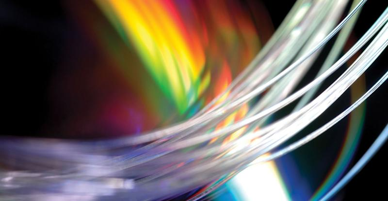 Colorful close-up of fiber-optic cables with light shining through the ends.