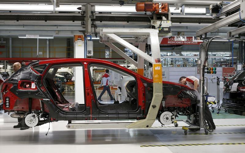 A worker from the SEAT factory, under the Volkswagen group, works on an engine of a SEAT Leon car, in Martorell near Barcelona