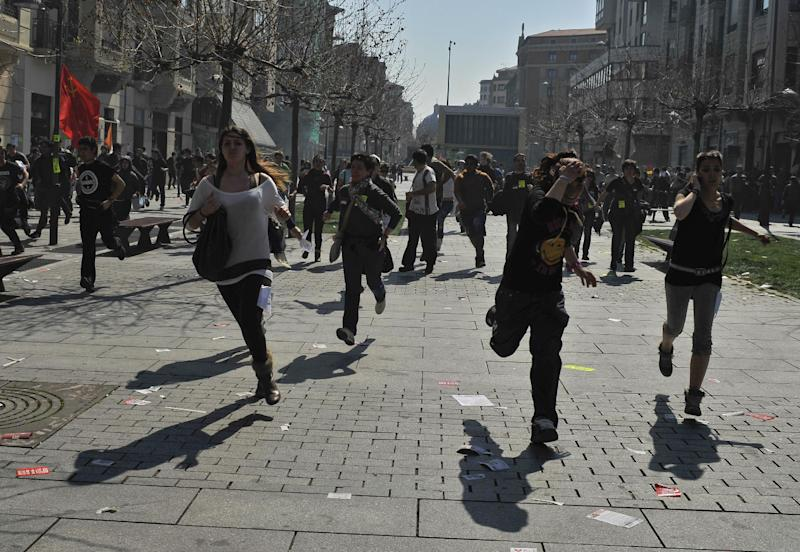 Demonstrators run on the street as they try to avoid riot police during the general strike to protest against the government's tough new labor reforms and cutbacks in Pamplona, northern Spain, Thursday, March 29, 2012. (AP Photo/Alvaro Barrientos)