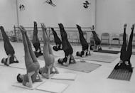 <p>Throughout the decade, yoga grew from a counter-culture practice to a common exercise for a svelte frame. Here, woman try a shoulder stand pose, which is said to increase thyroid activity. </p>