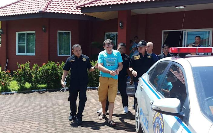 Francesco Galdelli (C) after he was arrested on the outskirts of Pattaya. An Italian who masqueraded as Hollywood superstar George Clooney to sell clothes online. - AFP