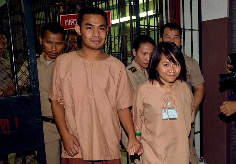 Thai student Patiwat Saraiyaem (left) and activist Porntip Mankong are escorted by prison guards after their verdict at the Criminal Court in Bangkok, on February 23, 2015 (AFP Photo/Pornchai Kittiwongsakul)