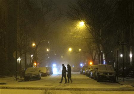 People walk through the West Village neighbourhood as snow begins to fall in New York January 2, 2014. REUTERS/Gary Hershorn