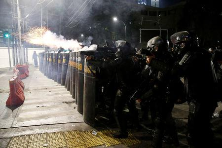 Mobile brigade (Brimob) police officers aim tear gas weapons during a clash with locals in Jakarta