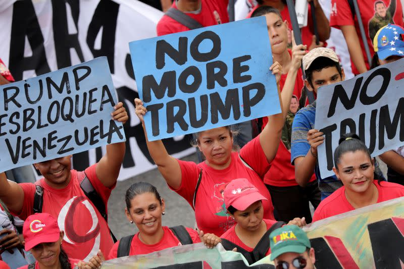 FILE PHOTO: Supporters of Venezuela's President Nicolas Maduro hold anti-trump banners during a rally against the U.S. sanctions on Venezuela, in Caracas