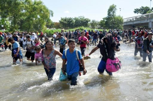 Central American migrants -- mostly Hondurans travelling in a caravan to the US -- cross the Suichate River between Guatemala and Mexico, where Mexican forces fired tear gas trying to force them back