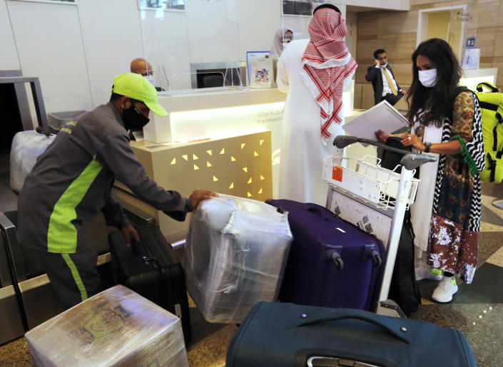 Saudi passenger Hanan Yousef, 35, checks her baggage for a trip to Egypt for tourism, at King Abdulaziz International Airport in Jiddah, Saudi Arabia, Monday, May 17, 2021. Vaccinated Saudis are allowed to leave the kingdom for the first time in more than a year as the country eases a ban on international travel that had been in place to try and contain the spread of the coronavirus and its new variants. (AP Photo/Amr Nabil)