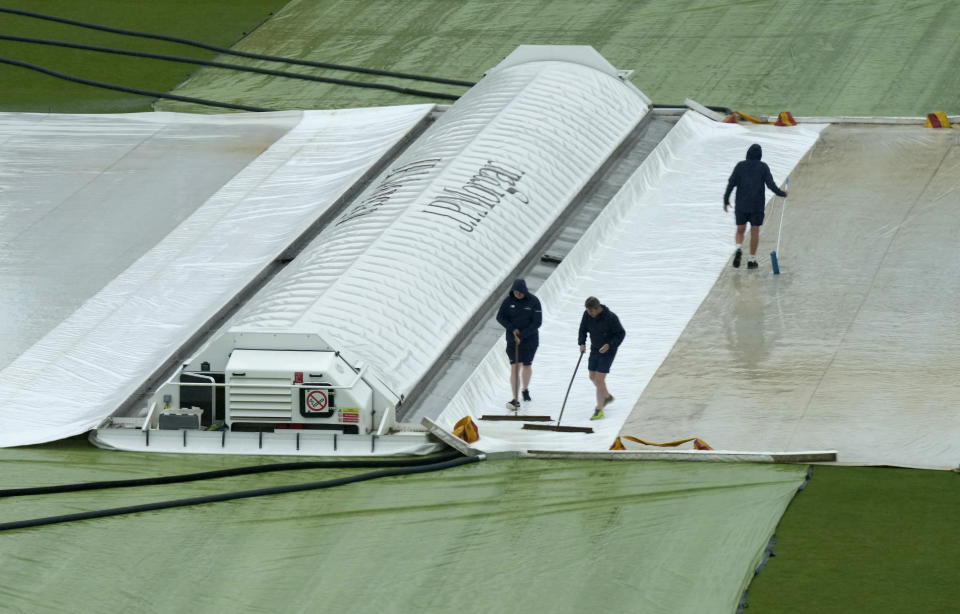 Groundsmen clear water off the rain covers protecting the pitch, as rain continues to delay the start of play on the third day of the Test match between England and New Zealand at Lord's cricket ground in London, Friday, June 4, 2021. (AP Photo/Kirsty Wigglesworth)