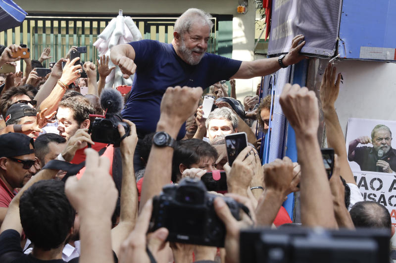 Brazilian former President Luiz Inacio Lula da Silva is carried aloft by supporters outside the Metal Workers Union headquarter in Sao Bernardo do Campo, Brazil, Saturday, April 7, 2018. Da Silva told supporters he will comply with an arrest warrant and turn himself in to police, to begin serving a sentence of 12 years and one month for a corruption conviction. (AP Photo/Andre Penner)
