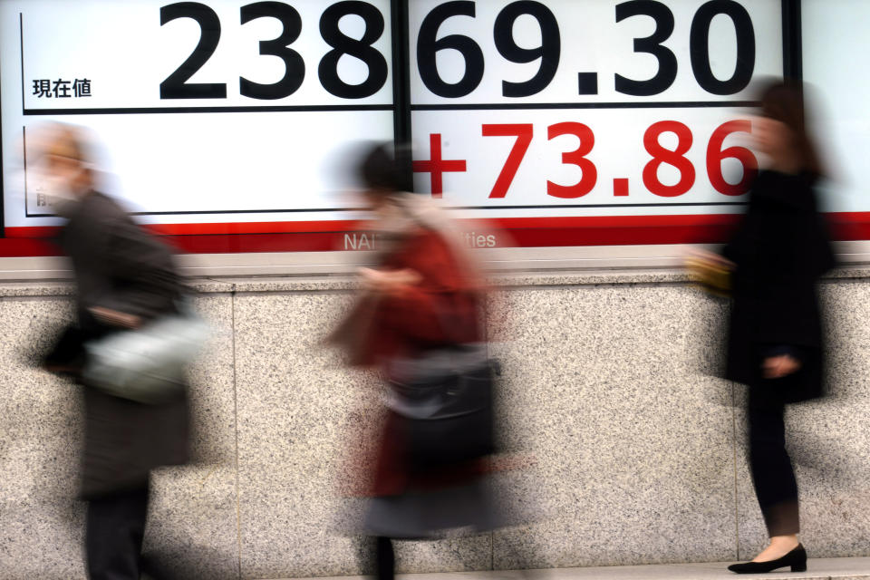 People walk past an electronic stock board showing Japan's Nikkei 225 index at a securities firm in Tokyo Friday, Jan. 24, 2020. Shares are mostly higher in quiet trading as China closes down for its week-long Lunar New Year festival. (AP Photo/Eugene Hoshiko)