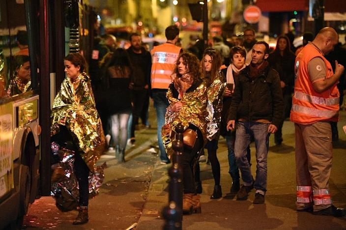 People are evacuated by bus, near the Bataclan concert hall in central Paris, on November 14, 2015 (AFP Photo/Martin Bureau)