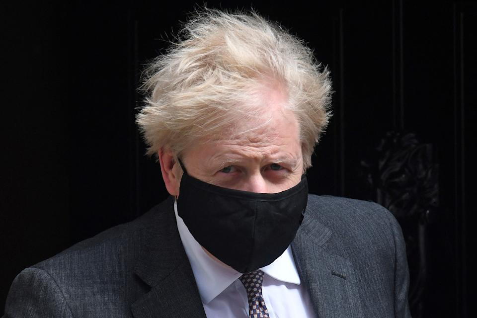 Britain's Prime Minister Boris Johnson, wearing a face mask to combat the spread of the novel coronavirus, leaves 10 Downing Street in central London on April 21, 2021, to take part in the weekly session of Prime Minister's Questions (PMQs) at the House of Commons. (Photo by DANIEL LEAL-OLIVAS / AFP) (Photo by DANIEL LEAL-OLIVAS/AFP via Getty Images)