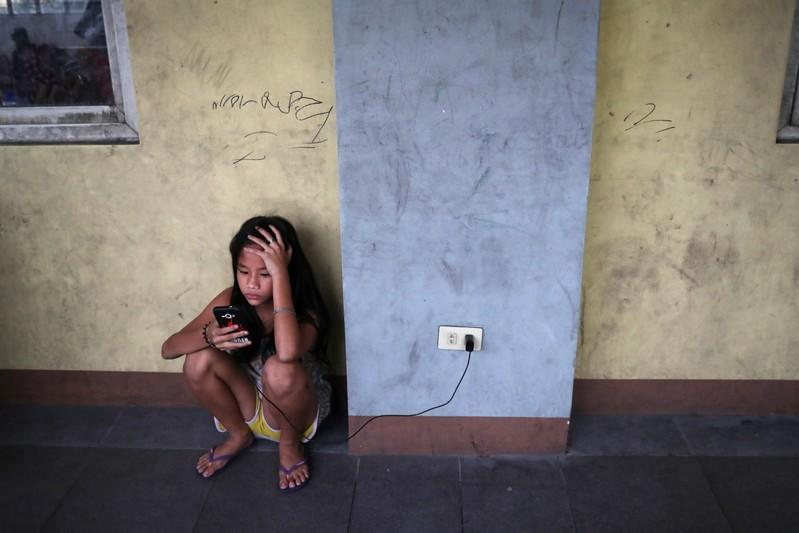 A girl charges her phone at the Delpan Evacuation Center after Typhoon Kammuri hit Metro Manila