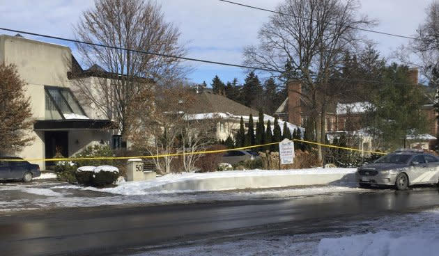 Police tape surrounds the home of billionaire Barry Sherman on Saturday.