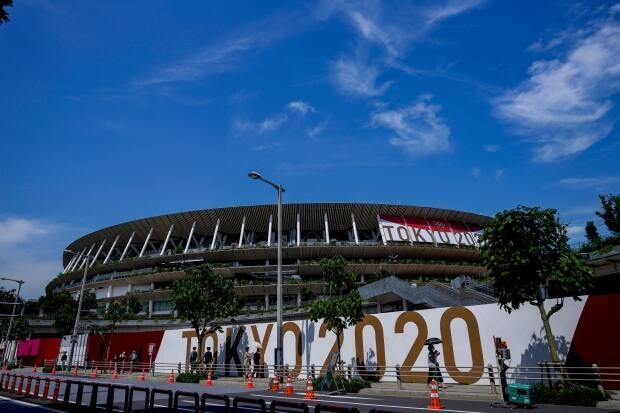 People wearing protective masks pass by National Stadium in early July, where the opening ceremony of the Olympic Games Tokyo 2020 will be held. (Kiichiro Sato/The Associated Press - image credit)