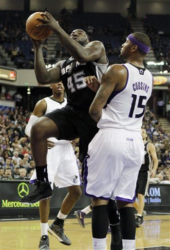 San Antonio Spurs' DeJuan Blair, left, goes to the basket against Sacramento Kings center DeMarcus Cousins during the first quarter of an NBA basketball game in Sacramento, Calif., Wednesday, March 28, 2012. (AP Photo/Rich Pedroncelli)