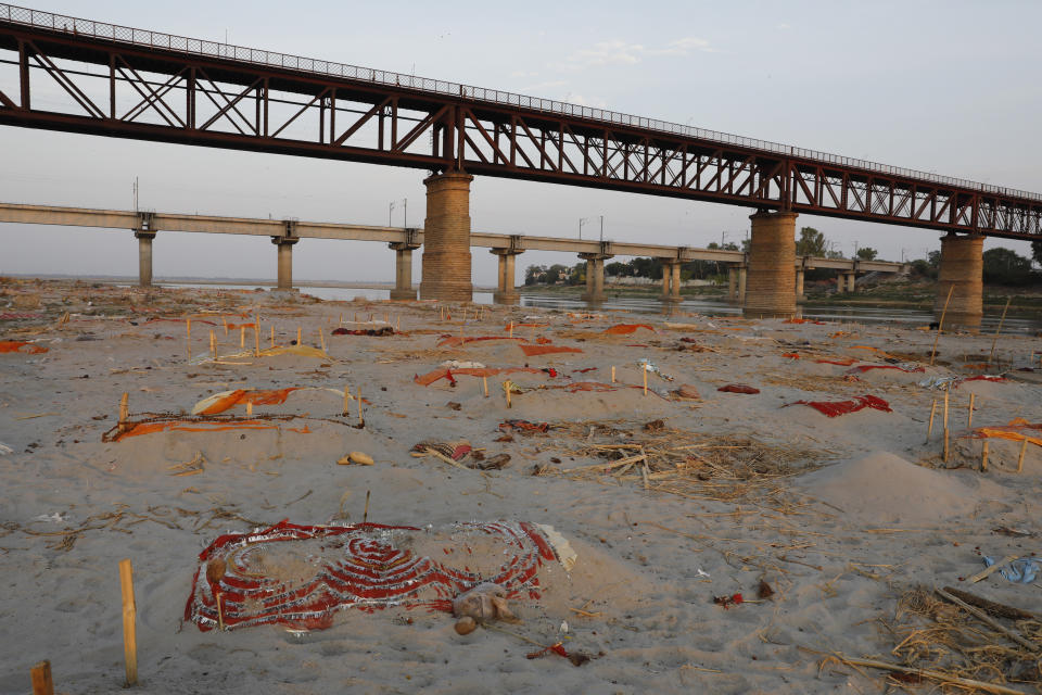 Bodies of suspected coronavirus victims are seen in shallow graves buried in the sand near a cremation ground on the banks of Ganges River in Prayagraj, India, Saturday, May 15, 2021. (AP Photo/Rajesh Kumar Singh)