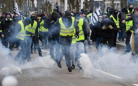 "Protesters run from tear gas fired by riot police during an anti-government demonstration called by the ""yellow vests"" (gilets jaunes) movement, on February 9, 2019 in Lorient, western France. - Credit:  FRED TANNEAU/AFP"